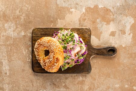 top view of fresh delicious bagel with meat, red onion and sprouts on wooden cutting board on aged beige surface Foto de archivo - 150126850