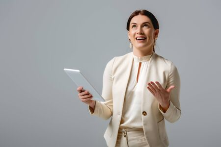 Positive businesswoman looking up during video call on digital tablet isolated on grey