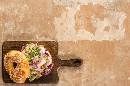 top view of fresh delicious bagel with meat, red onion and sprouts on wooden cutting board on aged beige surface