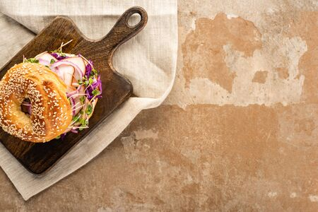 top view of fresh delicious bagel with meat, red onion and sprouts on wooden cutting board on napkin on aged beige surface Foto de archivo - 150126858
