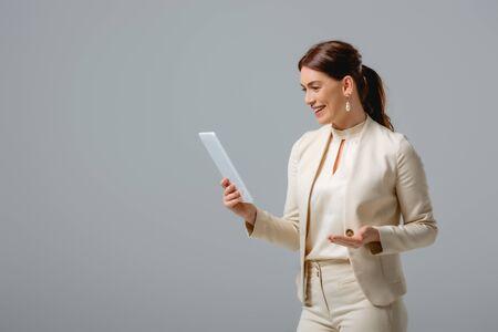 Beautiful businesswoman smiling while holding digital tablet isolated on grey Foto de archivo