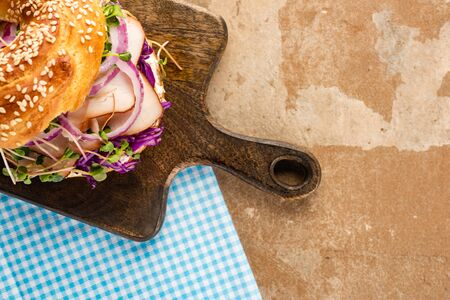 top view of fresh delicious bagel with meat, red onion, cream cheese and sprouts on wooden cutting board and plaid blue napkin Foto de archivo - 150126900