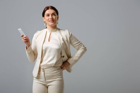 Beautiful businesswoman smiling away while holding smartphone isolated on grey Foto de archivo - 150126905