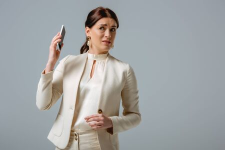 Confused woman in formal wear holding smartphone isolated on grey