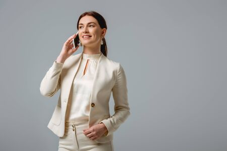 Attractive woman in formal wear smiling while talking on smartphone isolated on grey Foto de archivo - 150126913