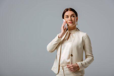 Beautiful businesswoman talking on smartphone isolated on grey