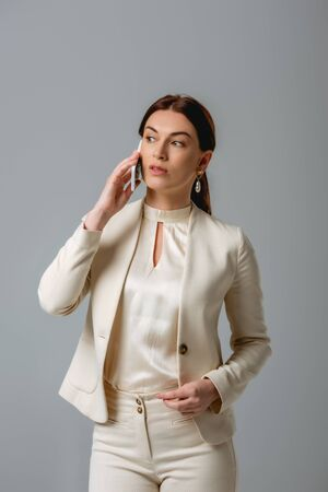 Beautiful businesswoman in formal wear talking on smartphone isolated on grey