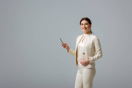 Beautiful woman in formal wear smiling at camera while holding smartphone isolated on grey Foto de archivo - 150126920