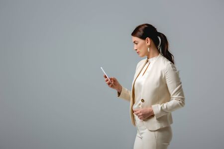 Side view of attractive businesswoman using smartphone isolated on grey Foto de archivo - 150126922