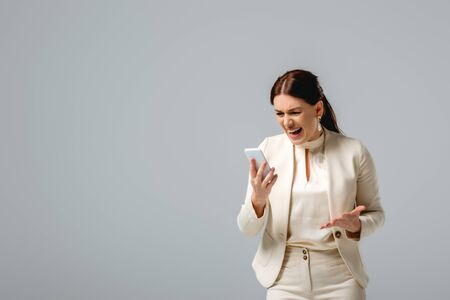 Aggressive businesswoman screaming while holding smartphone isolated on grey