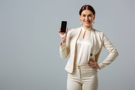 Beautiful woman in formal wear smiling at camera and showing smartphone with blank screen isolated on grey Foto de archivo - 150126937