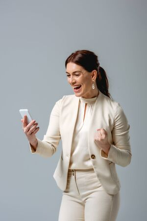Cheerful businesswoman showing yeah gesture while holding smartphone isolated on grey