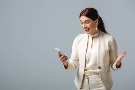 Happy businesswoman holding smartphone isolated on grey, concept of body positive Foto de archivo