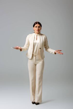 Confused businesswoman holding smartphone and looking at camera on grey background, concept of body positive Foto de archivo