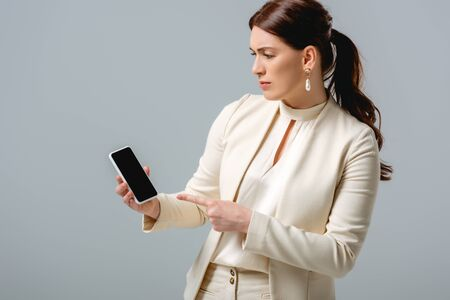 Beautiful woman in formal wear pointing with finger at smartphone isolated on grey