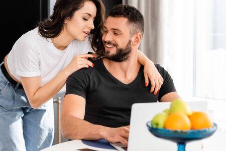 selective focus of beautiful woman hugging happy boyfriend near laptop