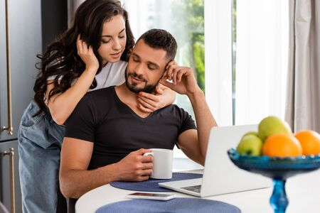 selective focus of beautiful woman hugging boyfriend with cup of coffee