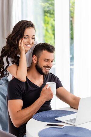 happy girl and handsome man looking at laptop near smartphone with blank screen 스톡 콘텐츠