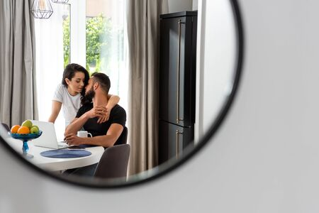selective focus of mirror with reflection of attractive girl hugging handsome boyfriend