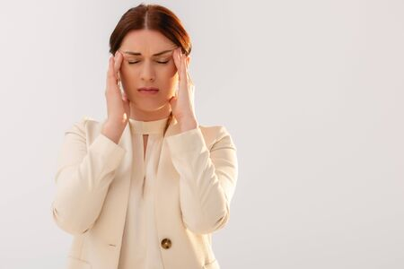 Beautiful businesswoman suffering from migraine isolated on grey