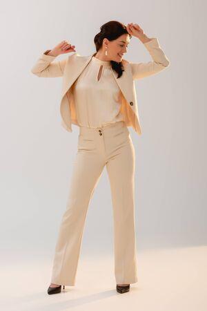 Positive businesswoman in formal wear dancing on grey background