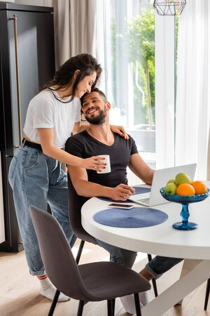 happy girl holding cup near cheerful freelancer boyfriend at home 스톡 콘텐츠