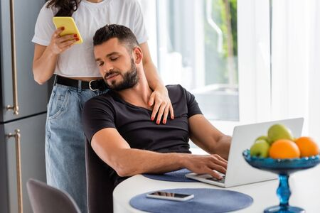 selective focus of woman standing and touching bearded freelancer boyfriend near laptop while using smartphone
