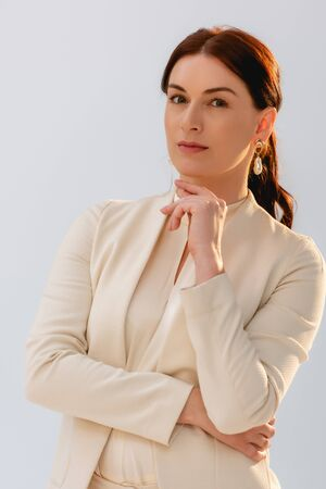 Beautiful businesswoman with hand near chin looking at camera isolated on grey Foto de archivo - 150127218