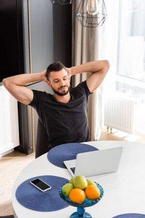 bearded freelancer looking at laptop near smartphone with blank screen on table