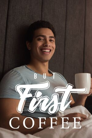 smiling mixed race man holding cup of coffee near but first coffee lettering in bedroom