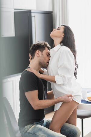 Selective focus of handsome man kissing and undressing sexy girlfriend during breakfast in kitchen Reklamní fotografie