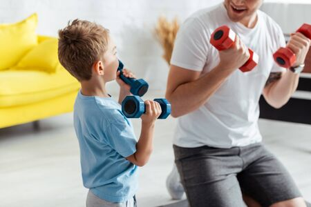 cropped view of man near son exercising with dumbbells at home Standard-Bild