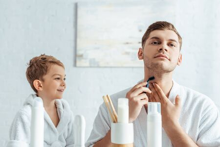 selective focus of young man shaving neck near smiling son in bathroom