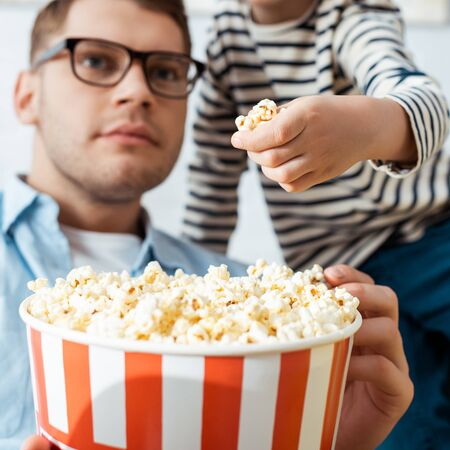 cropped view of boy taking popcorn from bucket while attentive father watching tv