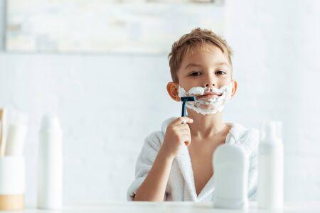 selective focus of cute boy shaving in bathroom near toiletries 写真素材 - 150486820