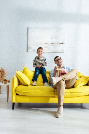 happy father and son sitting on yellow sofa, watching tv and eating popcorn