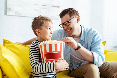 happy father and son looking at each other while eating popcorn from bucket Stock Photo
