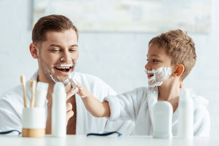 selective focus of smiling boy applying shaving foam on face of cheerful father 写真素材 - 150485652