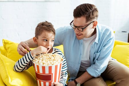 happy father looking at son eating popcorn from bucket Stock Photo