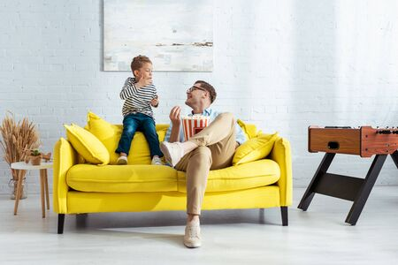 happy father and son eating popcorn while sitting on yellow sofa