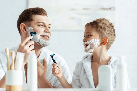 selective focus of smiling boy with foam on face looking at shaving father 写真素材 - 150485594