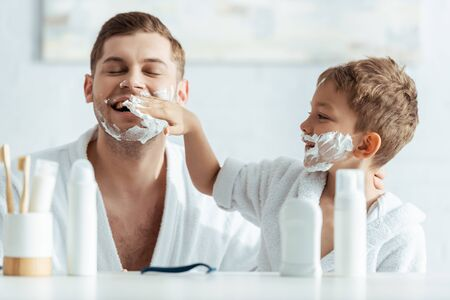 selective focus of smiling boy applying shaving foam on fathers face 写真素材 - 150485631