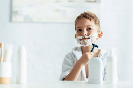 selective focus of cute boy shaving in bathroom near toiletries 写真素材