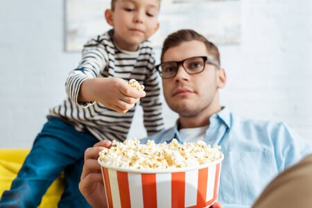 selective focus of cute boy taking popcorn from bucket while concentrated father watching tv