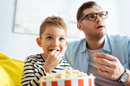 attentive father and son watching tv and eating popcorn at home