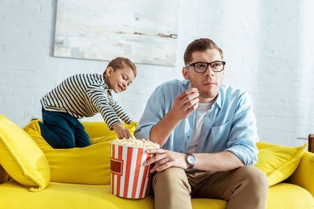 smiling boy taking popcorn from bucket while attentive father watching tv