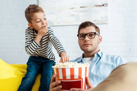 cute boy taking popcorn from bucket while concentrated father watching tv Stock Photo