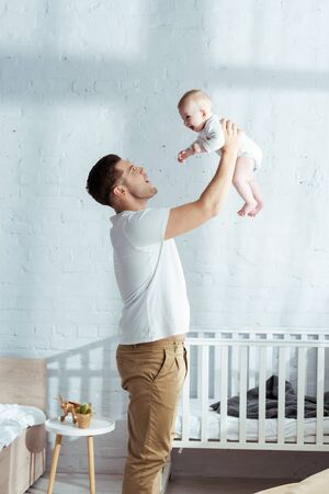 happy father holding adorable baby boy in outstretched hands near baby cot