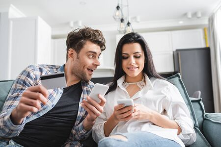 Selective focus of positive man holding credit card and looking at girlfriend using smartphone at home