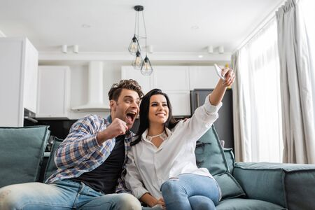 Selective focus of smiling woman taking selfie with smartphone near excited boyfriend showing yeah gesture at home